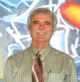 Image of Jeff King standing alone in front of a blue and white mural with a red sunburst to the right and above his head.